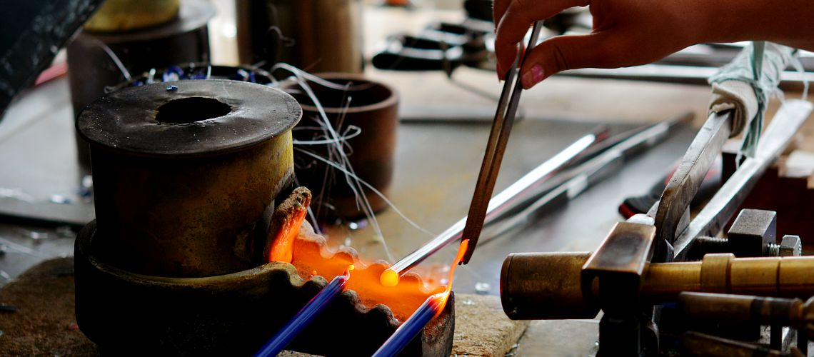 Material – glass rods – are being heated up in fire.